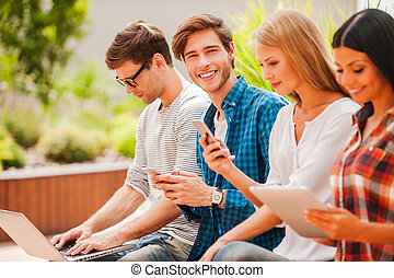 Living a digital life. Group of young people holding different digital devices while man looking at camera and holding mobile phone