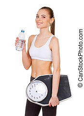 Living a healthy life. Attractive young woman in sports clothing holding weight scale and bottle with water while standing isolated on white