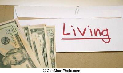 Living costs concept - USD bills on Living cash envelope