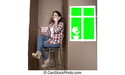 Living in a cardboard box. Happy woman talking on the phone ...
