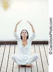 Living in balance with world. Beautiful young woman in white clothing sitting in lotus position and keeping arms raised while meditating outdoors
