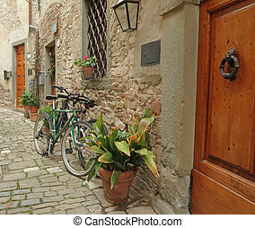 living in Tuscany, doorway to the tuscan house with parked...