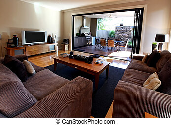 View from living room out onto patio with outdoor kitchen and barbecue. Stylish modern living.