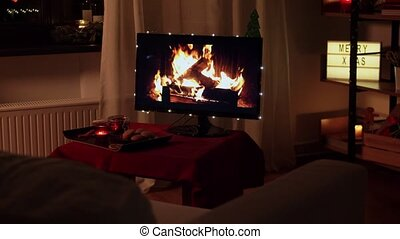 winter holidays, christmas and interior concept - tv monitor used as fireplace in decorated dark living room at cozy home