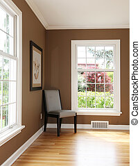 Living room corner with chair and two windows and hardwood floor.