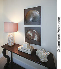 Dark brown wood table with lamp, decorative shell and boxes. Shiny pictures on the wall