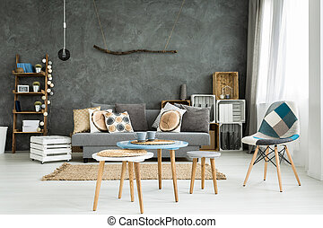 Modern minimalistic and bright living room in shades of cyan with sofa full of cushions, chair, three coffee tables, carpet and stillage made of wooden cases