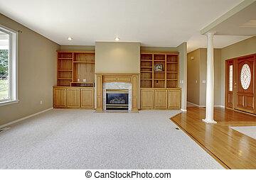 Living room in open floor plan with foyer view and wooden entrance door.