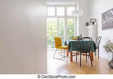 Living room interior with long table with green table cloth and different kind of chairs, black map on the wall, real photo with copy space