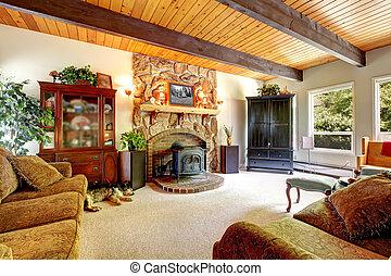 Living room of the farm house with wood ceiling and stone fireplace.