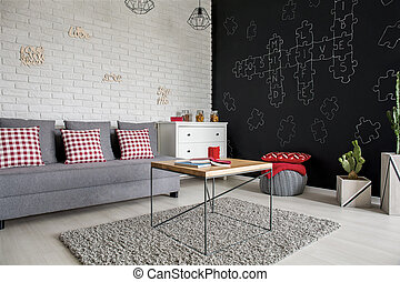 Living room with blackboard wall, sofa and dresser