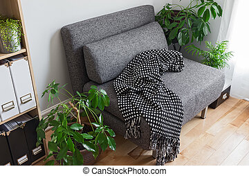 Living room with bright plants and gray armchair