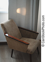 Living room with cozy chair. Interior design concept. Neutral interior with retro armchair on beige background. Real photo