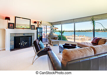 Living room with fireplace and water view with large windows.