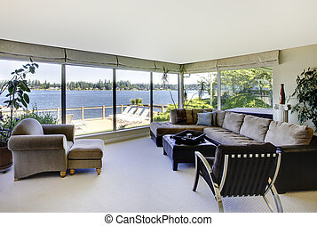 Living room with fireplace, modern furniture and water view with large windows.