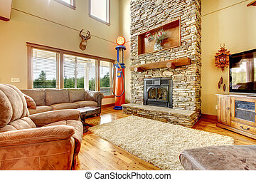 Living room with high ceiling, stone fireplace and leather ...