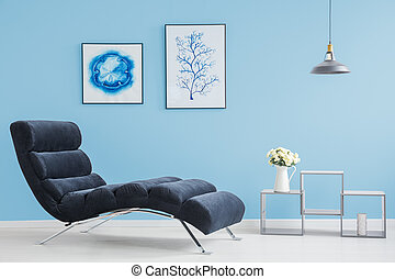 Living room with two pictures on blue wall and modern...
