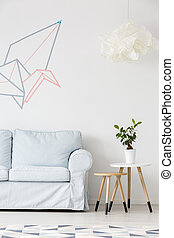 Light living room with sofa, pattern carpet, side table and washi tape wall decor