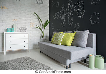 Living room with white dresser, sofa and blackboard wall