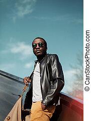 llevando, ciudad, moda, elegante, cuero, encima, cielo, joven, chaqueta, bolsa, tarde, negro, hombre africano