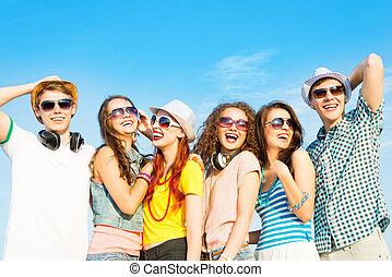 llevando, grupo, gente, joven, gafas de sol, sombrero