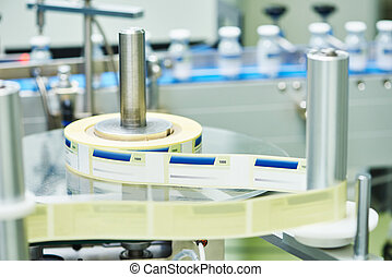 pharmaceutical industry. Glass bottles ampoules going through the labeling machinery at pharmacy manufacture factory