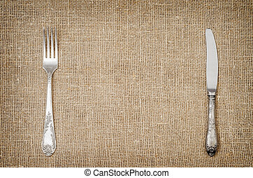 Llinen background with old silver fork and knife