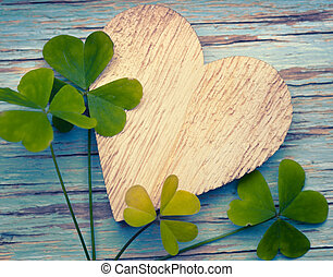 Llucky clovers with an old wooden heart on a blue vintage wood b