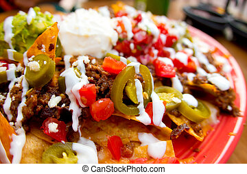 Mexican appetizer of nacho chips loaded with beef, cheese and jalapenos