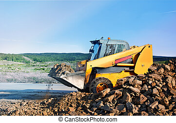 Loader dumping stone on road on the natural background In the countryside.
