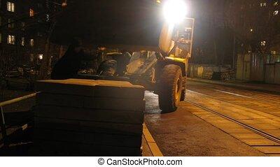 Loader-excavator board concrete slabs at street blocking way for trams