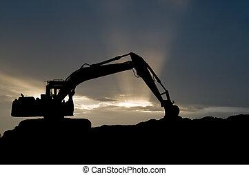 silhouette of loader excavator scoop shovel over scenic sunset