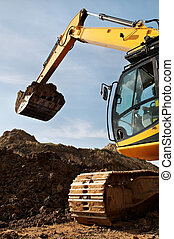 Loader Excavator standing in sandpit with risen bucket over cloudscape sky