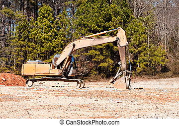 Loader in Field by Pine Trees