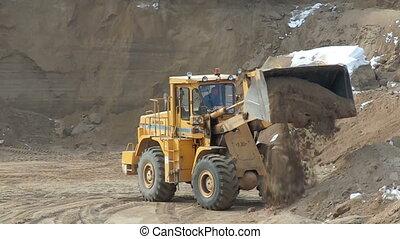 Loader machine unloading sand at construction site