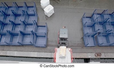 Loader moves backward from cargo and second ride away, view...