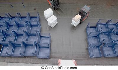 Loader moves tray with cargo and second stands near, view...