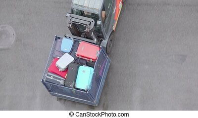 Loader moves tray with passengers luggage, view from above