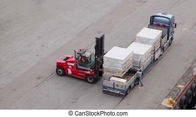 Loader unload truck, labourer walk around and help, view...