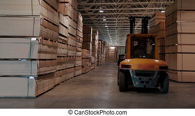 Loader working at warehouse in lumber factory