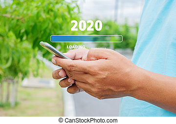 Loading 2020 with young man using a smartphone