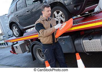 loading broken car on a tow truck on a roadside