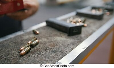 Loading bullets to pistol gun in shooting gallery, close up