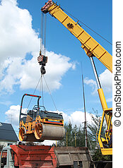 Loading compactor on the transportation machine using a crane