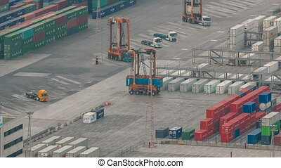 Loading containers on a sea cargo ship timelapse tracking shot, view of the cargo port and container terminal of Barcelona with the Montjuic hill, Barcelona, Catalonia, Spain.
