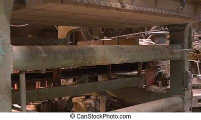 Loading finished batch of bricks on conveyor, close-up view