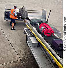 Loading luggage onto plane - A man is loading luggage onto...