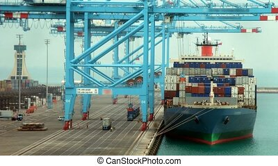 Loading of cargoes on the cargo ship on landing stage. Time lapse