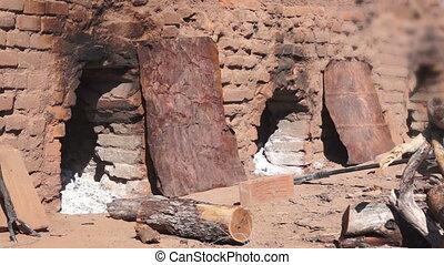 Loading Oven for Adobe Brick Making - Man loading a...