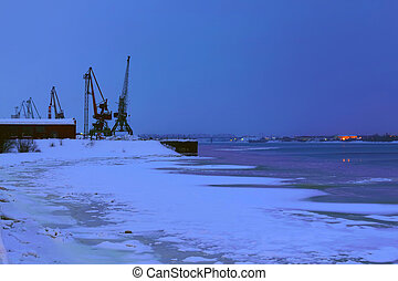 Loading pier with cranes on the frozen river at night